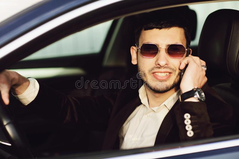 Den unga bussinesmanen i dr?kt och svarta exponeringsglas talar vid telefonen i hans bil r r royaltyfri fotografi