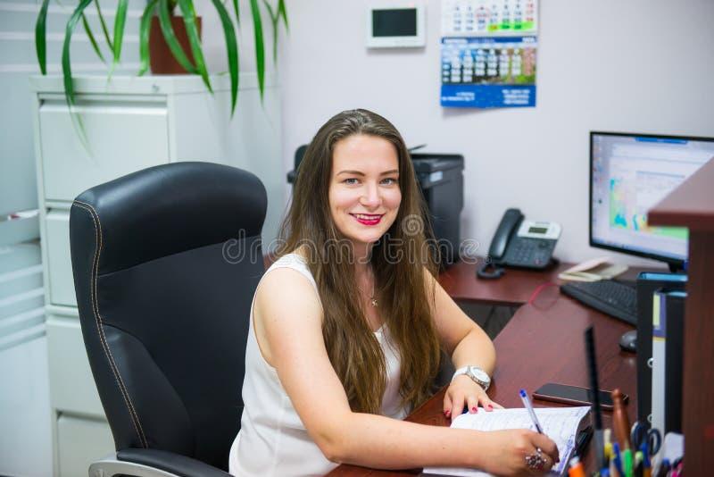 Den unga caucasian affärsdamen ser kameran och ler, medan sitta på hennes arbetsplats i regeringsställning Kvinnligt egenföretaga royaltyfria foton
