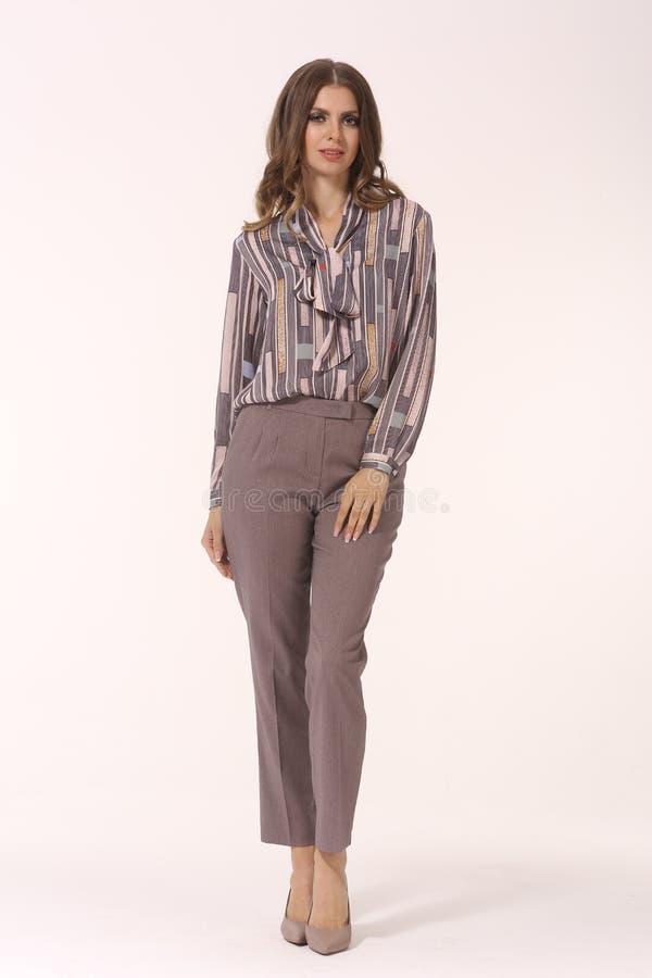 Den unga caucasian affärskvinnaledaren som poserar i längd för kropp för skor för tryckblus och för stilett för höga häl för byxa arkivfoton