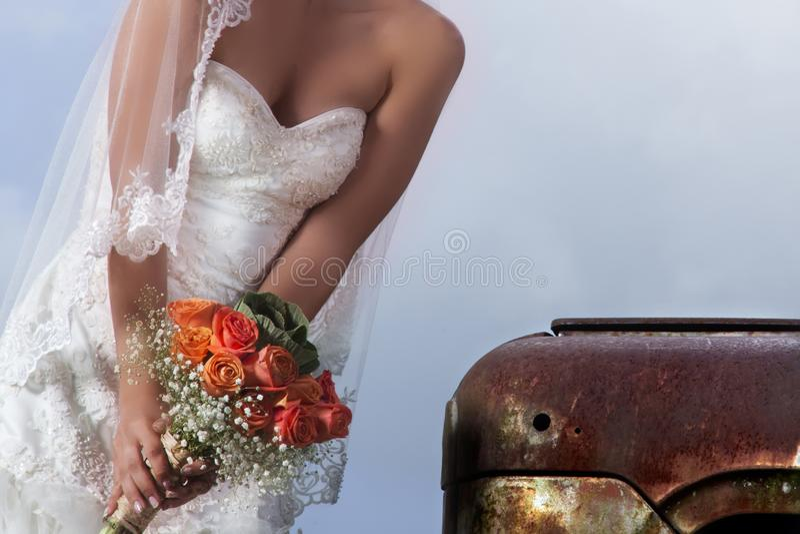 Den unga caucasian bruden som bär en spets- bröllopsklänning och innehav en rund och vibrerande bukett av sommar, blommar framme royaltyfri foto