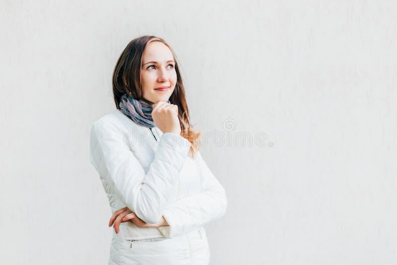 Den unga Caucasian brunetten ser bort trycka på hänsynsfullt hakan på den monokromma väggen för bakgrund arkivfoto