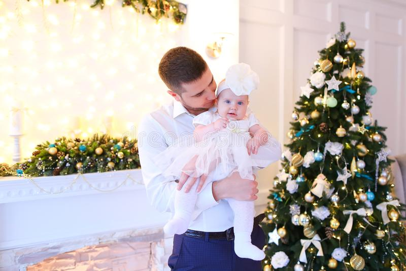 Den unga caucasian fadern som håller den lilla kvinnlign, behandla som ett barn nära julgranen och den dekorerade spisen arkivbilder