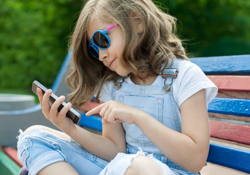 Den unga caucasian flickan med lockigt hår som sitter på, parkerar och använder den smarta telefonen Lyckligt le barn som läser e arkivfoton