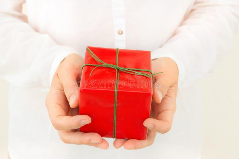 Den unga caucasian kvinnan rymmer i handgåvaasken som slås in i rött papper som binds med det gröna bandet Ensam fryst tree Jul arkivfoto