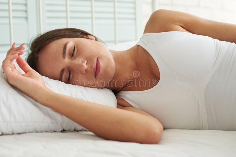 Den unga Caucasian kvinnan som sover i koppla av, poserar i sängen arkivfoton