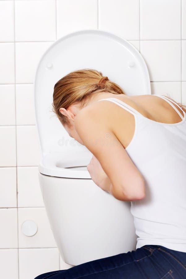 Den unga caucasian kvinnan spyr i badrummet. royaltyfri bild