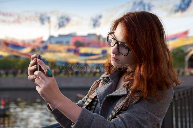 Den unga caucasian kvinnan tar fotoet med smartphonen i parkera Turismtema Utomhus- plats royaltyfri foto