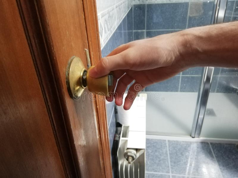 Den unga caucasian mannen öppnar badrumdörren Hand på door& x27; s-handtagslut upp Dusch med blåa tegelplattor i bakgrund arkivfoton