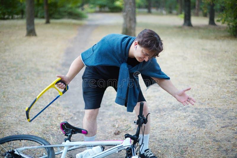 Den unga caucasian mannen med mörkt hår förbereder sig till sågen som cykeln som lägger på jordningen, i övergett, parkerar med s royaltyfria foton
