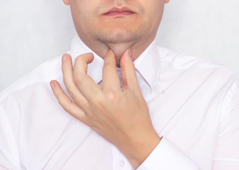 Den unga caucasian mannen rymmer sig upp för en fet dubbelhaka, begrepp av uppladdning och övning mot en dubbelhaka fotografering för bildbyråer