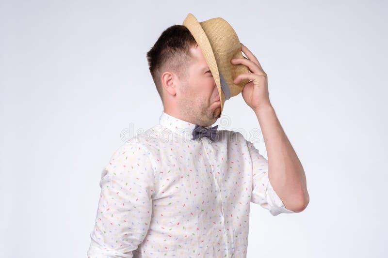 Den unga caucasian mannen stänger framsidan med hatten som försöker att bli anonymen arkivfoton