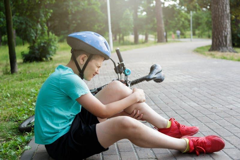 Den unga caucasian pojken i hjälm och grön t-skjorta fick olycka och sitter på jordningen, når han har fallit från cykeln och kän royaltyfria bilder