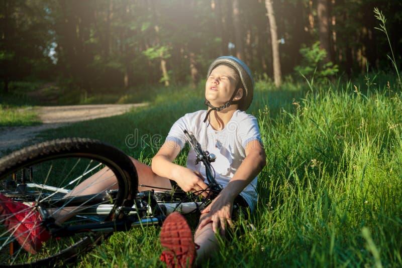Den unga caucasian pojken i hjälm och den vita t-skjortan fick olycka och sitter på jordningen, når han har fallit från cykeln oc arkivbilder