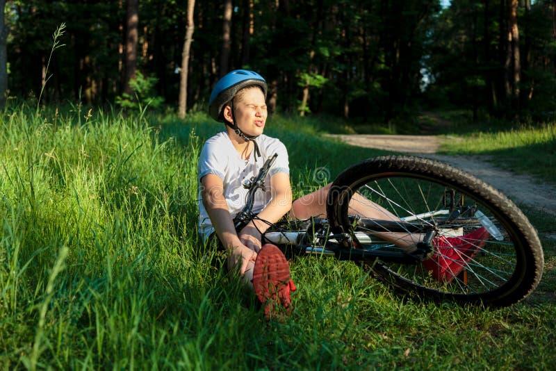 Den unga caucasian pojken i hjälm och den vita t-skjortan fick olycka och sitter på jordningen, når han har fallit från cykeln oc royaltyfri foto