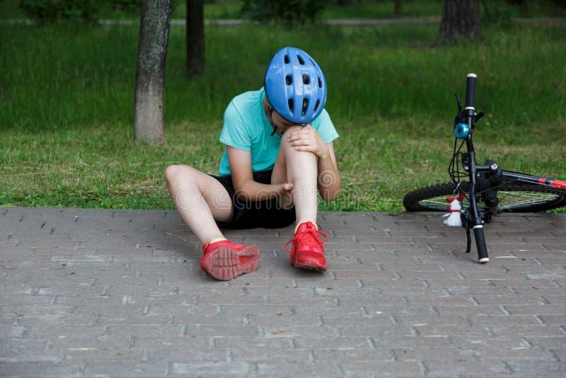 Den unga caucasian pojken i hjälm och den vita t-skjortan fick olycka och sitter på jordningen, når han har fallit från cykeln oc arkivfoto