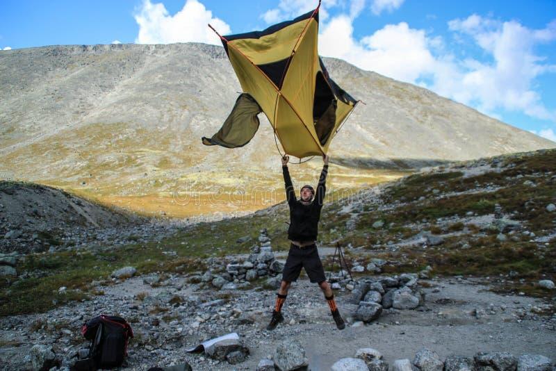 Den unga Caucasian vit manturisten hoppar och rymmer ett tält i hans händer som lyfter det högt ovanför honom bland bergen arkivfoton