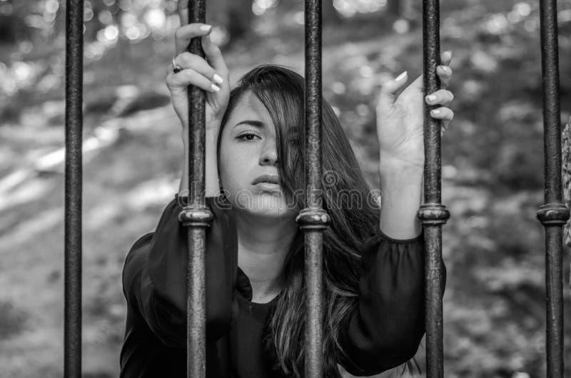 Den unga charmiga flickan tonåringen med långt hårsammanträde bak stänger i fängelsefånge i en medeltida arrest med ledset och at royaltyfri bild