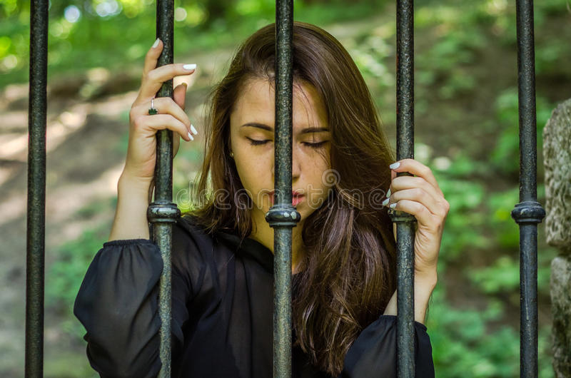 Den unga charmiga flickan tonåringen med långt hårsammanträde bak stänger i fängelsefånge i en medeltida arrest med ledset och at royaltyfri foto