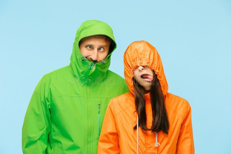 Den unga couplelen som poserar på studion i höstomslag som isoleras på blått arkivfoto
