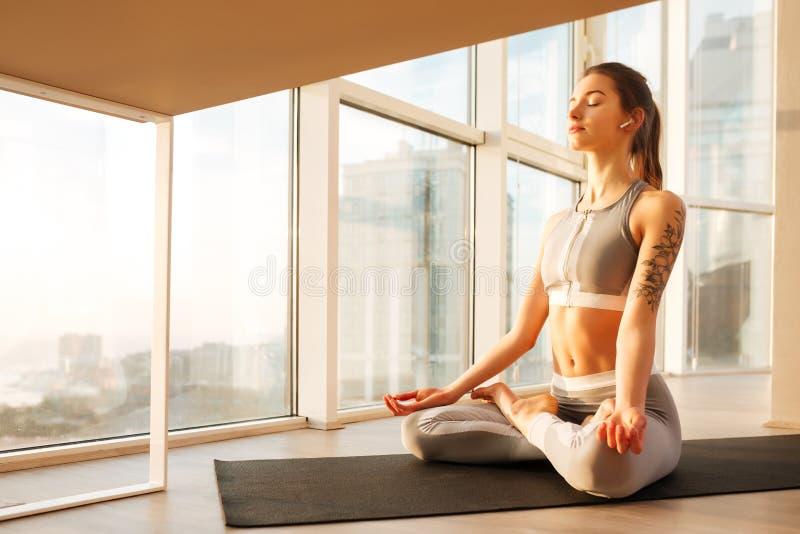 Den unga damen i sportig överkant och damasker som sitter i lotusblomma, poserar att meditera på yoga som är matt över fönster royaltyfri bild
