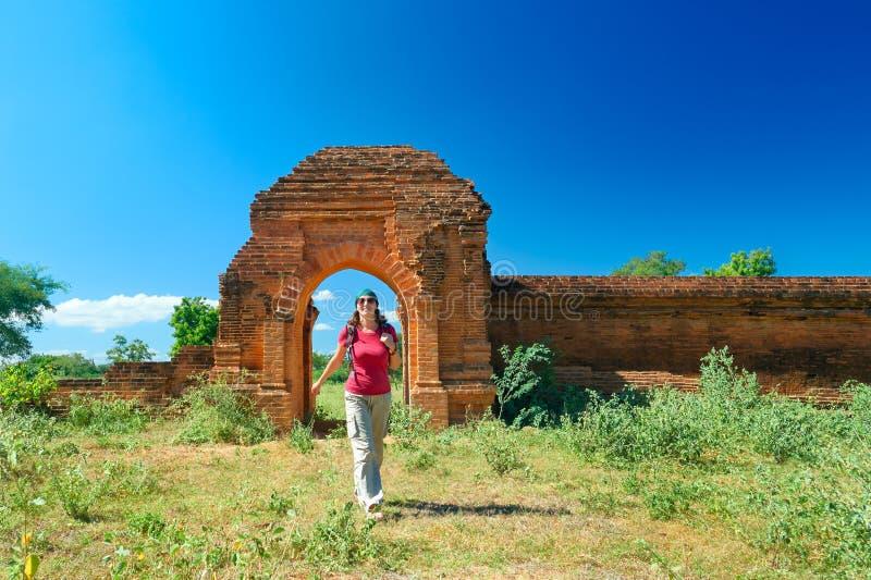 Den unga damen med en ryggsäck ut ur portarna av det forntida fördärvar royaltyfri bild