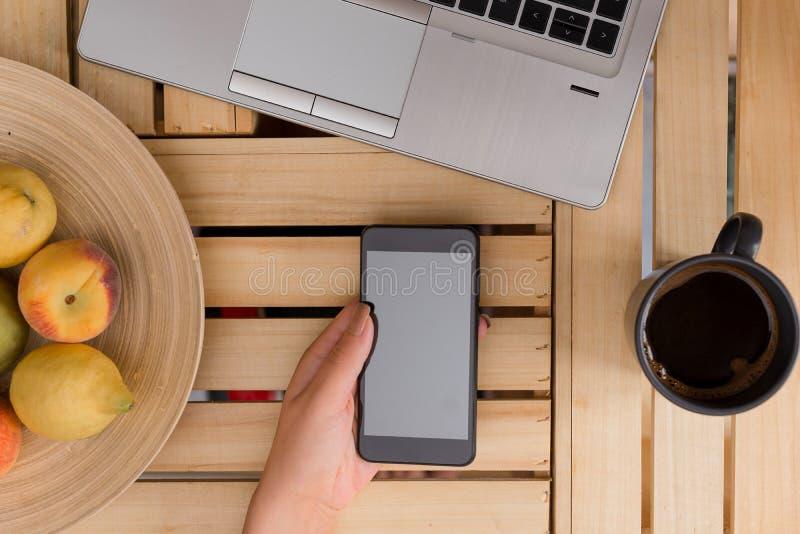 Den unga damen som använder och rymmer en mörk smartphone i en spjällådatabell med, rånar av svart kaffe Kontorstillförsel, mobil arkivfoto