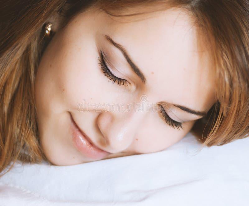 Den unga damen sover på sängen royaltyfri fotografi