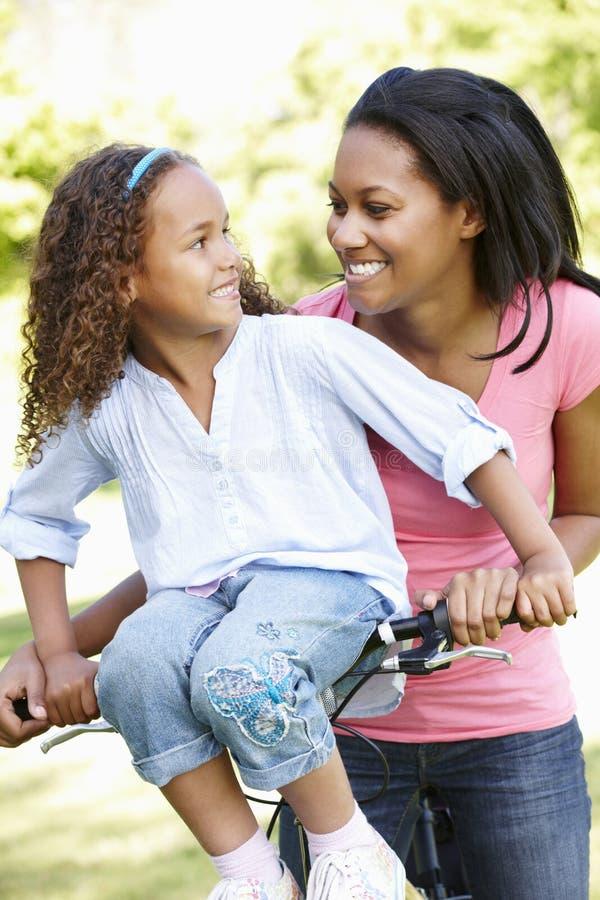 Den unga den afrikansk amerikanmodern och dottern som in cyklar, parkerar royaltyfria bilder