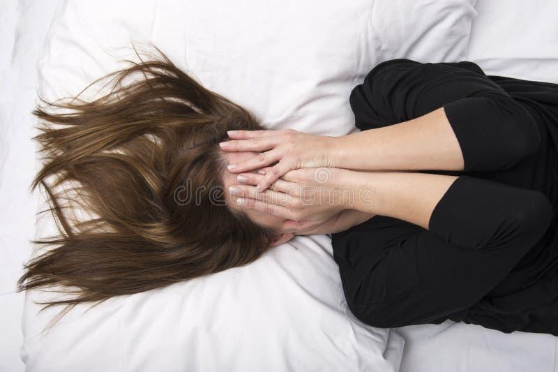 Den unga deprimerade kvinnan ligger i hennes säng som täcker hennes framsida med henne händer royaltyfria bilder