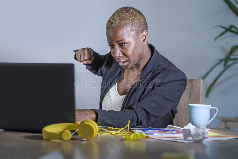 Den unga desperata och stressade afrikansk amerikanaffärskvinnan som arbetar på känsla för spänningen för lidande för kontorsskri arkivfoton