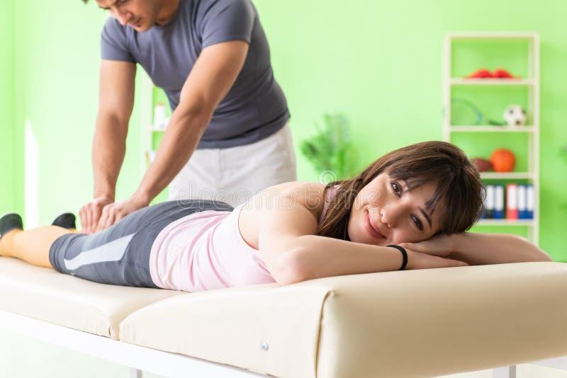Den unga doktorskiropraktorn som masserar patienten royaltyfria bilder