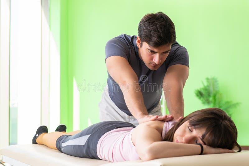 Den unga doktorskiropraktorn som masserar patienten royaltyfri fotografi