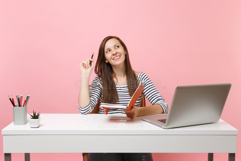 Den unga drömlika kvinnan som ser tänka upp söka den nya idéinnehavblyertspennan, och anteckningsboken sitter arbete på det vita  royaltyfri foto