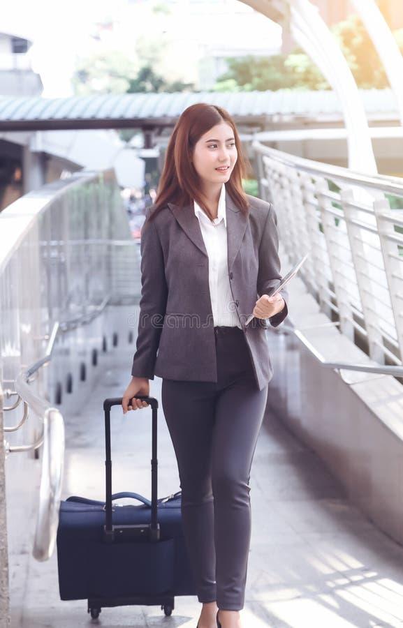 Den unga eleganta affärskvinnan med handbagage och minnestavlan är waen royaltyfria bilder