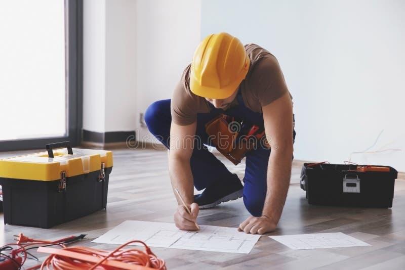 Den unga elektrikeren som kontrollerar teckningar, near toolboxes royaltyfria bilder