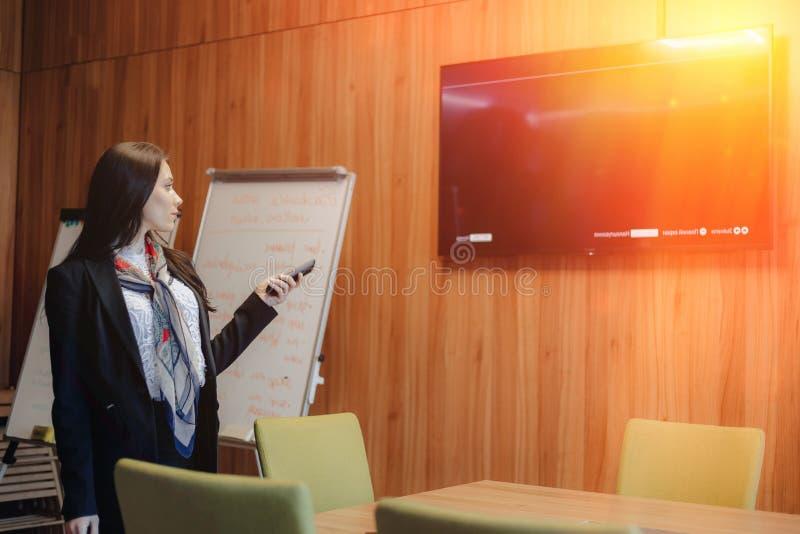 Den unga emotionella attraktiva flickan i affärsstilen av kläder kopplar fjärrkontrollen till TV:N i kontoret eller arkivbild