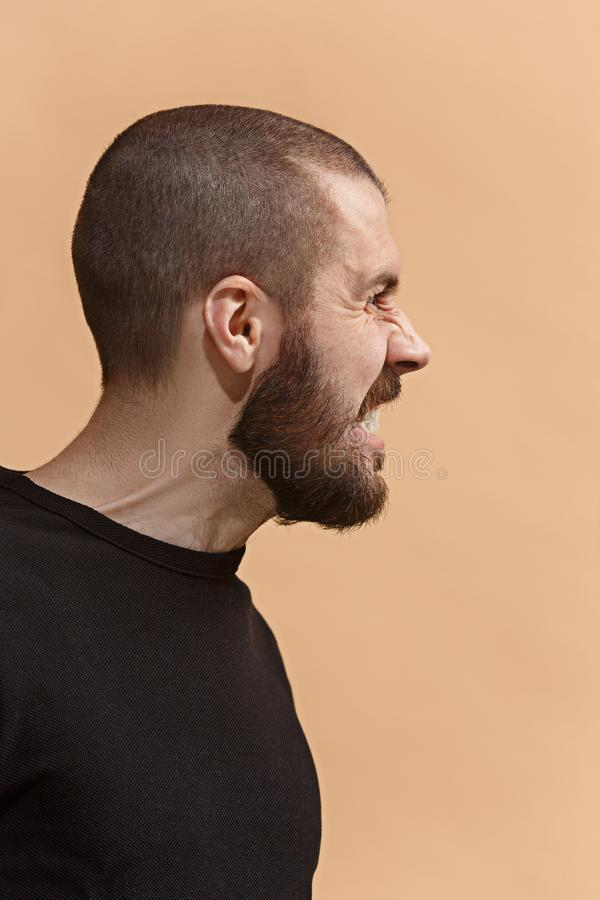 Den unga emotionella ilskna galna mannen på pastellfärgad studiobakgrund arkivfoton