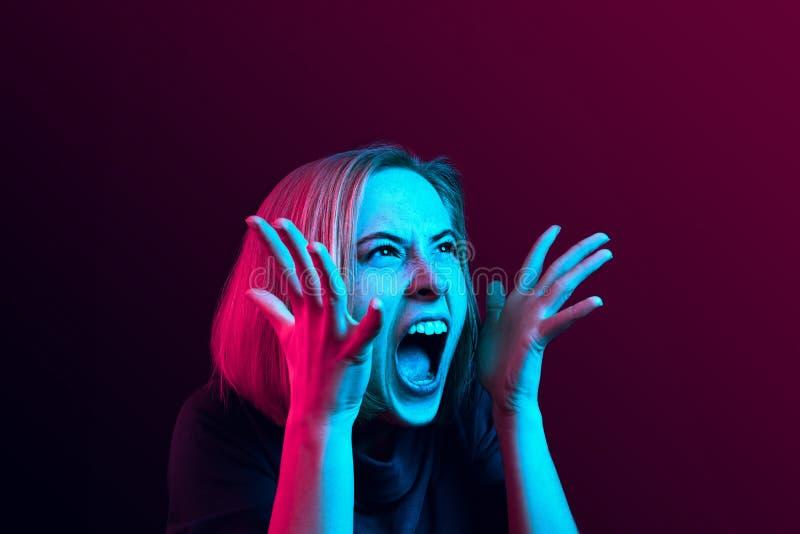 Den unga emotionella ilskna kvinnan som skriker på neonstudiobakgrund fotografering för bildbyråer