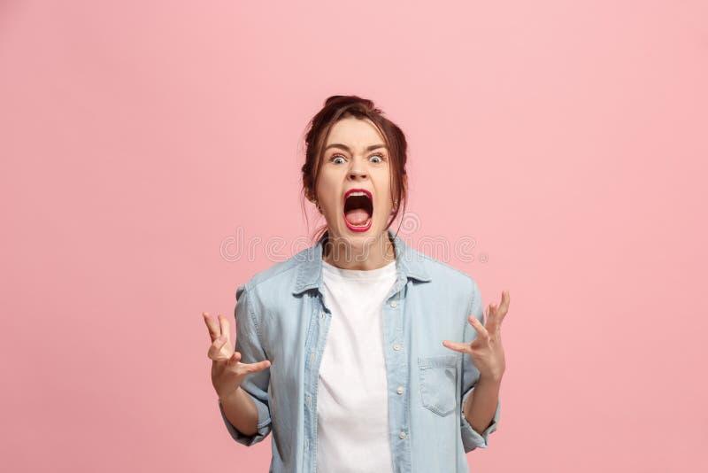 Den unga emotionella ilskna kvinnan som skriker på rosa studiobakgrund arkivfoton