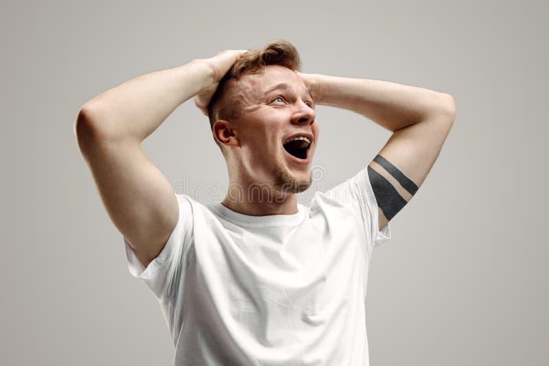 Den unga emotionella ilskna mannen som skriker på garay studiobakgrund fotografering för bildbyråer