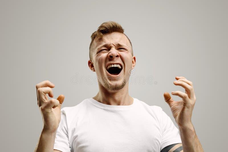 Den unga emotionella ilskna mannen som skriker på garay studiobakgrund royaltyfria foton
