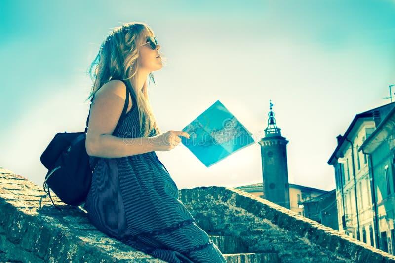 Den unga enkla kvinnliga turisten i en gammal italiensk stad kallade Comacchio den retro stil filtrerade bilden arkivfoton