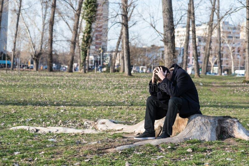 Den unga ensamma deprimerade och angelägna mannen som bara sitter i, parkerar på trästubben som svikas i hans liv som gråter och  royaltyfria bilder