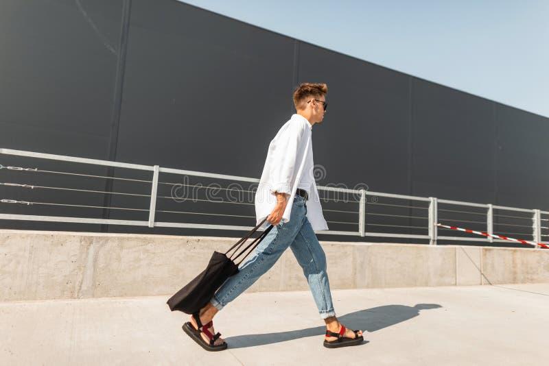 Den unga europeiska hipstermannen i en vit skjorta i jeans i trendiga sandaler med en svart påse går på gatan royaltyfri foto