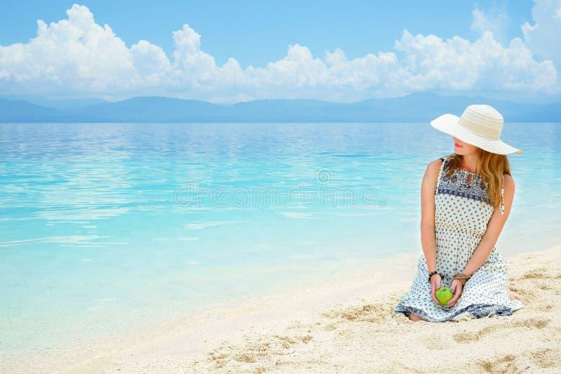 Den unga europeiska kvinnan i klänningen, hatt och med det gröna äpplet sitter på sandstranden av det lugna tropiska havet på den royaltyfria foton