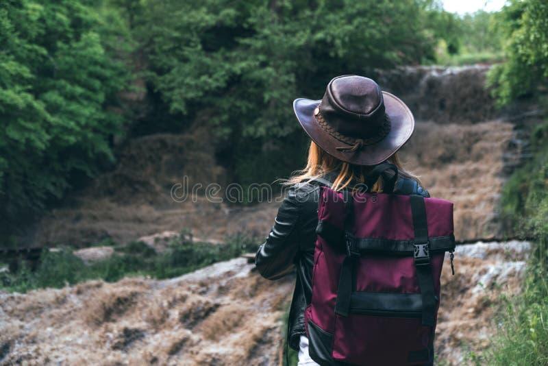 Den unga europeiska kvinnliga turisten med ryggsäck- och cowboyhatten som ser floden, tvättade bort bron, korsningen var royaltyfri bild