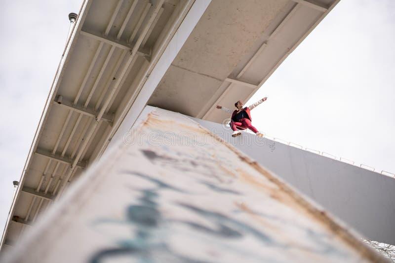 Den unga extremal oförskräckta kvinnan klättrar upp under bron och hagyckeln Farliga trick och riskera utan försäkring royaltyfri fotografi