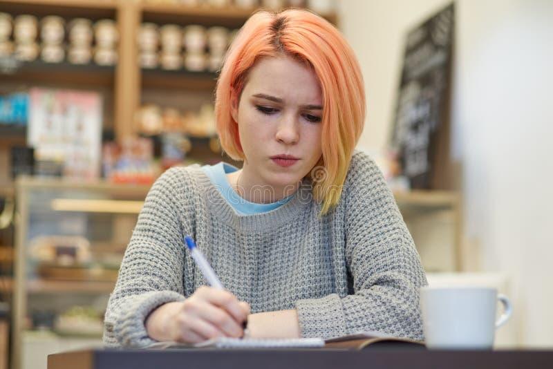 Den unga författaren för studentflickaskolflickan gör anmärkningar i hans anteckningsbok arkivbild