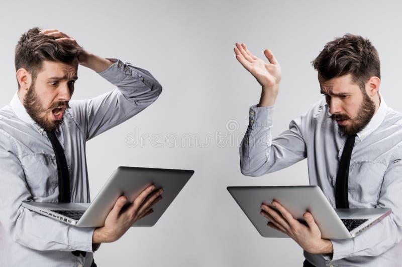 Den unga förvirrade och frustrerade mannen med hans bärbar datordator arkivfoton