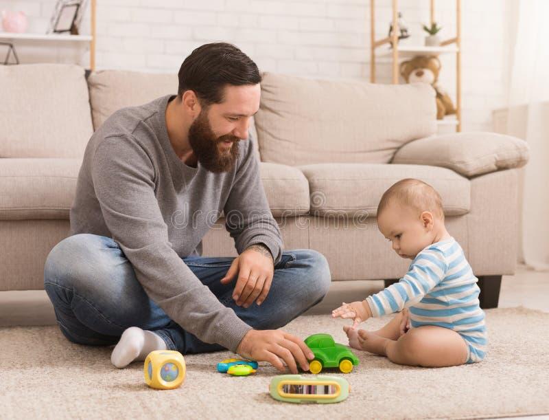 Den unga fadern och hans behandla som ett barn pojken som spelar med leksakbilen royaltyfri bild